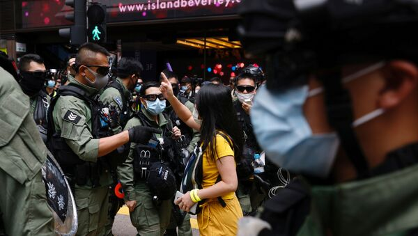 A pro-democracy protester argues with police before a protest urging the release of twelve Hong Kong activists, detained on the Chinese mainland, who were arrested at sea after attempting to flee to Taiwan, on Chinese National Day in Hong Kong, China October 1, 2020. - Sputnik International