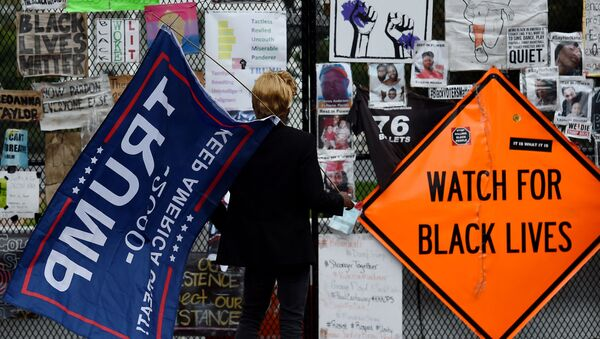 A supporter of US President Donald Trump arrives at Black Lives Matter Plaza in Washington, DC, on 10 October 2020, before a speech by the American President at the White House. - Sputnik International
