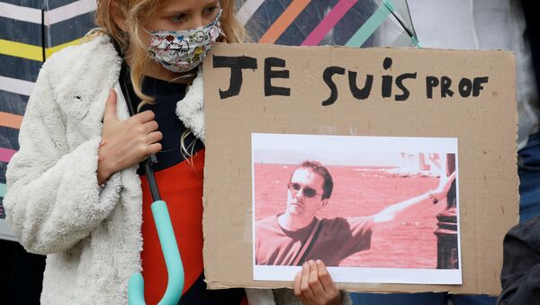 A girl holds a banner with a picture of Samuel Paty, the French teacher who was beheaded on the streets of the Paris suburb of Conflans St Honorine, during a tribute at the Place de la Republique, in Lille, France, October 18, 2020. REUTERS/Pascal Rossignol       NO RESALES. NO ARCHIVES. - Sputnik International