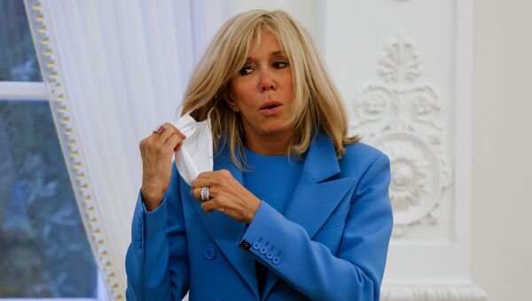In this file photo taken on September 28, 2020, French President's wife Brigitte Macron takes off her face mask after a welcoming ceremony at the Presidential Palace in Vilnius, Lithuania. - Brigitte Macron has gone into a 7-day self-isolation period after being in contact with a person who has been tested positive with Covid-19, her entourage told AFP on October 19, 2020. Brigitte Macron, who does not show any symptoms of the disease, was in contact on October 15 with a person declared positive for Covid-19 on October 19, and showing symptoms, according to her entourage.  - Sputnik International
