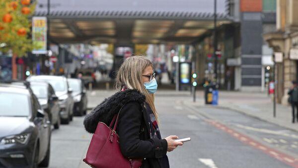 A woman wearing a face mask walks in Manchester, England, Monday, Oct. 19, 2020 - Sputnik International