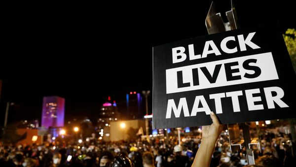 A demonstrator holds up a Black Lives Matter sign during a protest over the death of a Black man, Daniel Prude, after police put a spit hood over his head during an arrest on March 23, in Rochester, New York, U.S. September 6, 2020 - Sputnik International