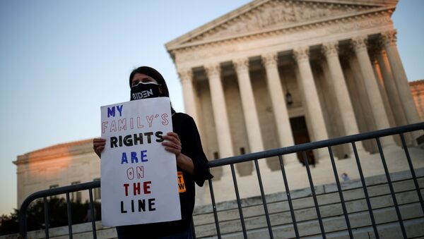 A person wearing a protective face mask reading Biden holds a placard in front of the U.S Supreme Court building, in Washington D.C., U.S., October 21, 2020.  - Sputnik International