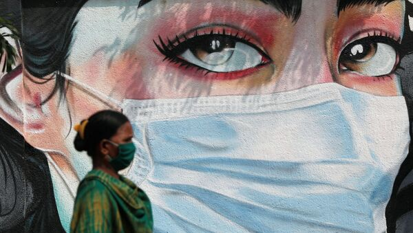 A woman walks past a graffiti of a girl wearing a protective mask amidst the spread of the coronavirus disease (COVID-19) in Mumbai, India, October 23, 2020 - Sputnik International