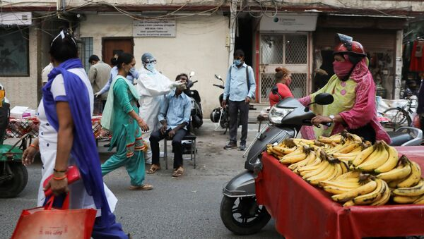 A healthcare worker wearing personal protective equipment (PPE) collects a swab sample from a man amidst the spread of COVID-19, at a weekly market in New Delhi - Sputnik International