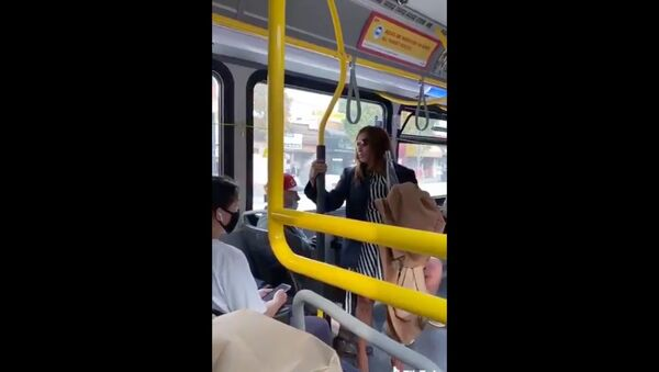 Cellphone footage captures moment a TransitLink commuter is pushed out of a stationary bus moments after spitting on a fellow traveler. The incident is being investigated by Canada's Metro Vancouver Transit Police. - Sputnik International