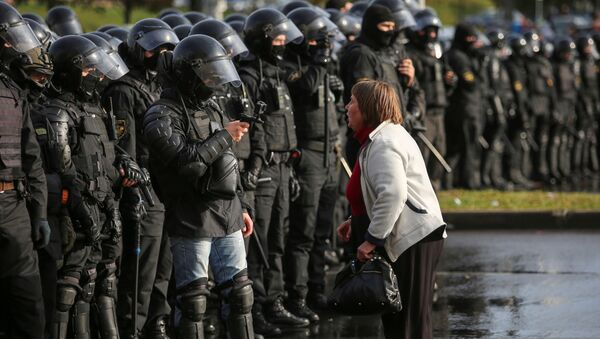 An opposition supporter argues with a police officer during an opposition rally to reject the presidential election results in Minsk, Belarus October 4, 2020.  - Sputnik International