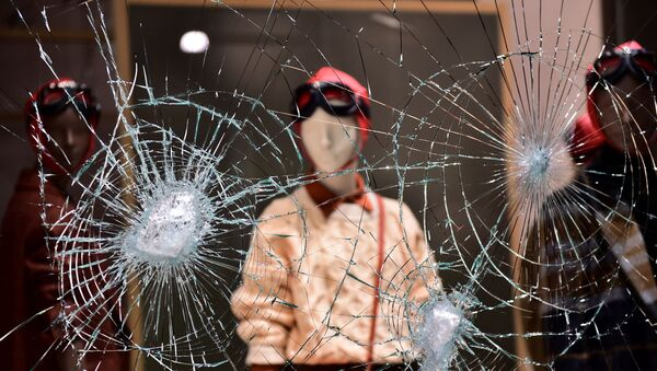 A damaged window of a store is seen as people protest against the new restrictions introduced by the government to curb the coronavirus disease (COVID-19) infections, in Turin, Italy, October 26, 2020. - Sputnik International