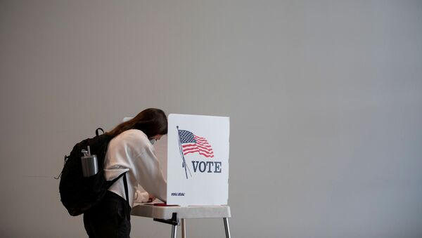 People cast their ballots for the upcoming presidential elections as early voting begins in Ann Arbor, Michigan, U.S., September 24, 2020. - Sputnik International