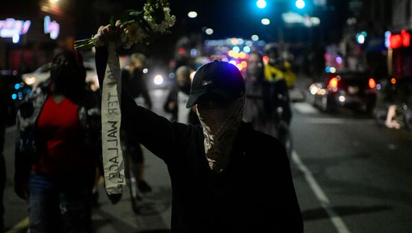 A demonstrator holds a bouquet of flowers during a rally after the death of Walter Wallace Jr., a Black man who was shot by police in Philadelphia, Pennsylvania, U.S., October 27, 2020. - Sputnik International