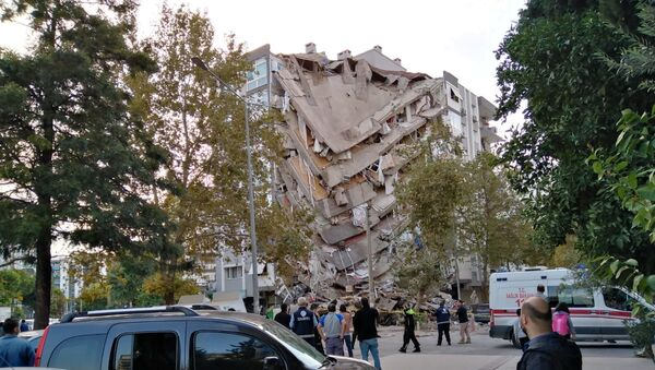Locals look at a damaged building after a strong earthquake struck the Aegean Sea on Friday and was felt in both Greece and Turkey, where some buildings collapsed in the coastal province of Izmir, Turkey, October 30, 2020 - Sputnik International