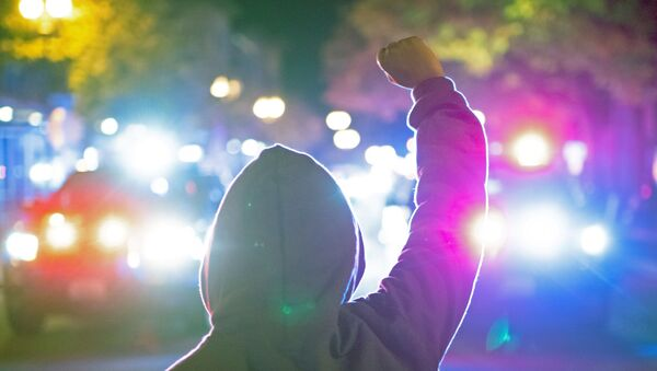 A woman holds up her fist as police declare an unlawful assembly after a vigil and march marking the shooting death by police of Black man Kevin E. Peterson Jr. in Vancouver, Washington - Sputnik International