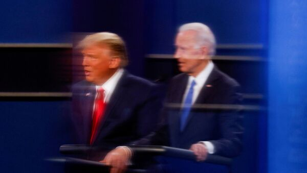 FILE PHOTO: U.S. President Donald Trump and Democratic presidential nominee Joe Biden are reflected in the plexiglass protecting a tv camera operator from covid as they participate in their second 2020 presidential campaign debate at Belmont University in Nashville, Tennessee, U.S., October 22, 2020 - Sputnik International
