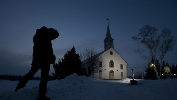 A journalist takes a photo of the church in La Motte, Quebec, at twilight Wednesday, 13 March 2013, in La Motte. THE CANADIAN PRESS/Adrian Wyld - Sputnik International