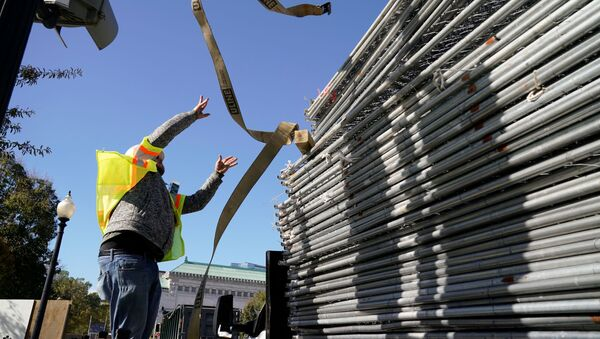 A workers works on a stack of fencing near a security checkpoint on the South side of the White House, the day before the U.S. presidential election, in Washington, U.S., November 2, 2020. - Sputnik International