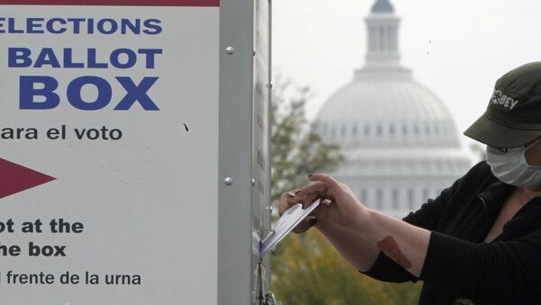With the dome of the US Capitol visible, a voter drops a ballot into an early voting drop box, Wednesday, 28 October 2020, at Union Market in Washington. - Sputnik International