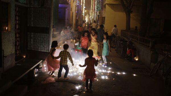 In this Wednesday, Nov. 11, 2015 photo, children burn fire crackers outside their houses in New Delhi, India - Sputnik International