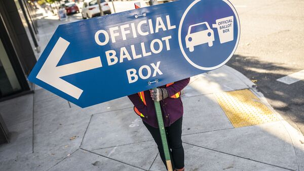 An election worker directs voters to a ballot drop off location on November 2, 2020 in Portland, Oregon. Oregons voting system allows for ballot processing before the start of Election Day.  - Sputnik International