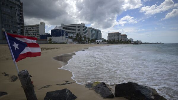 A Puerto Rican flag flies on an empty beach at Ocean Park, in San Juan, Puerto Rico, Thursday, May 21, 2020. Puerto Rico is cautiously reopening beaches, restaurants, churches, malls, and hair salons under strict conditions as the U.S. territory emerges from a two-month lockdown despite dozens of new coronavirus cases reported daily.  - Sputnik International