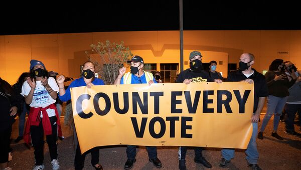 Counter-protesters, organized by Make the Road Action Nevada and PLAN Action, hold a banner during a Stop the Steal protest by supporters of U.S. President Donald Trump at the Clark County Election Center in North Las Vegas, Nevada, U.S. November 4, 2020.  - Sputnik International