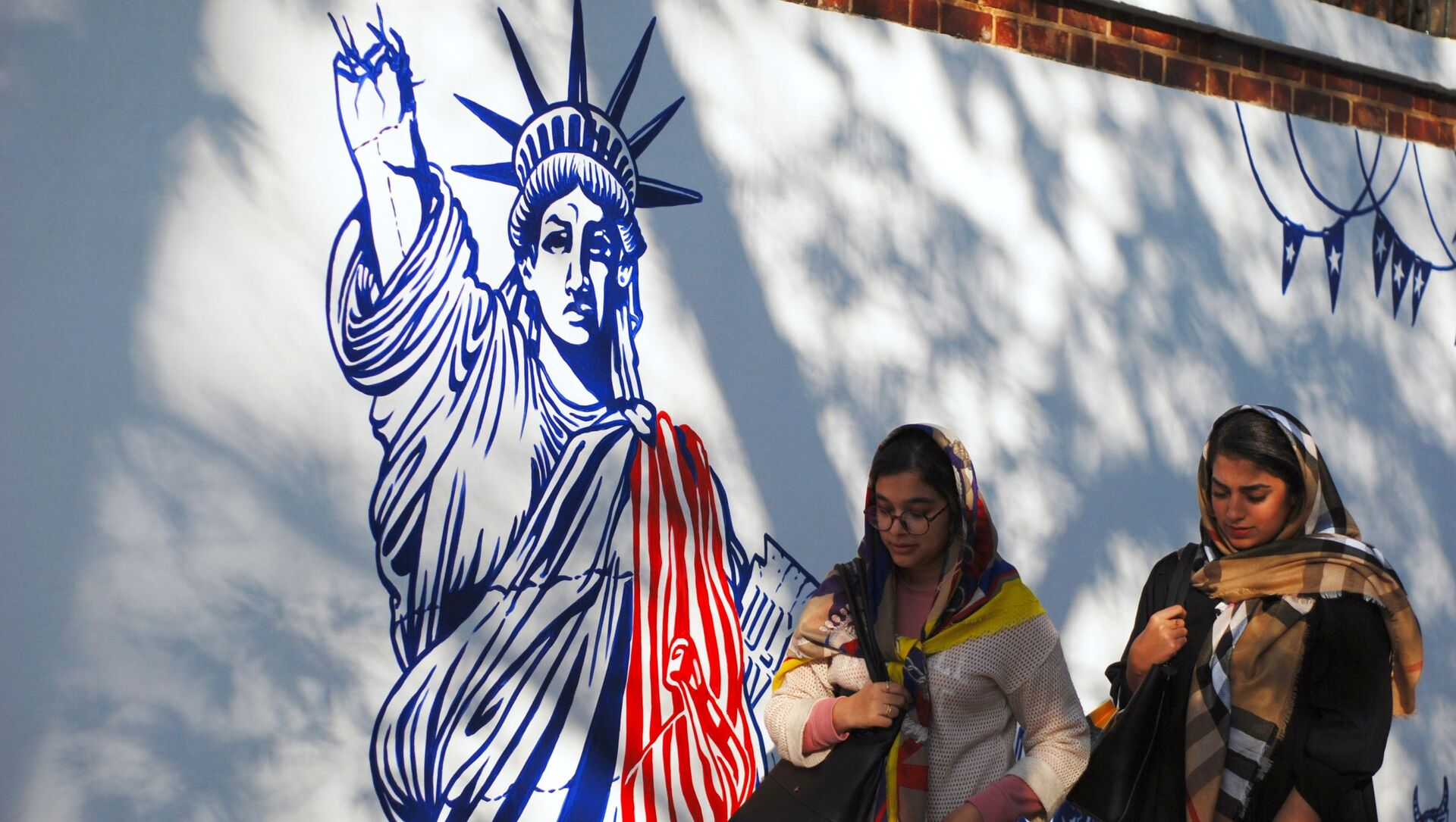 Women walk by a mural on the walls of the former US Embassy compound in Tehran. File photo. - Sputnik International, 1920, 04.09.2021