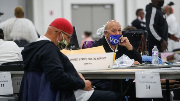 A man wearing a Vote mask looks on as votes continue to be counted at the TCF Center the day after the 2020 U.S. presidential election, in Detroit, Michigan, U.S., November 4, 2020. - Sputnik International