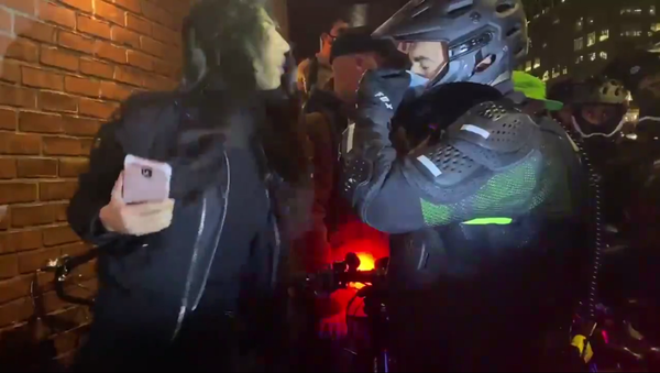 """A screenshot from a video of a woman spitting in the face of a New York City Police Department sergeant on 4 November 2020 during a """"Count Every Vote"""" protest in the West Village neighborhood of the borough of Manhattan, New York City, following the US 2020 presidential election. - Sputnik International"""