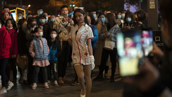 A young woman dressed as a nurse struts in a crowd gathered during Halloween night at a shopping district in Beijing on Saturday, 31 October 2020. Although Halloween is not traditionally celebrated in China, some residents in the Chinese capital took the time to dress up for a bit of fun.  - Sputnik International