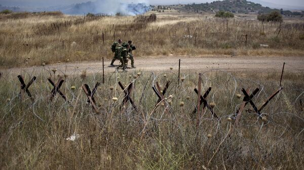 Israeli soldiers walk back from a position on the border with Syria on the Israeli controlled Golan Heights as smoke rises following explosions, Tuesday, July 16, 2013. - Sputnik International