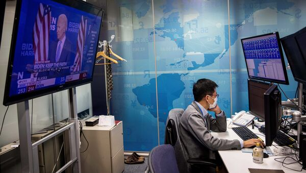 A currency trader works at his desk as a screen (L) shows news updates on the US presidential election featuring an image of Democratic Party candidate Joe Biden, at a foreign exchange trading company in Tokyo on November 5, 2020 - Sputnik International