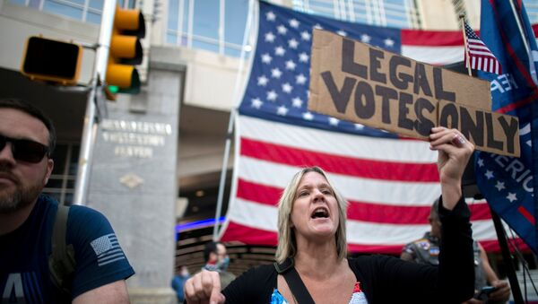 Carri Dusza, a supporter of President Donald Trump, holds a placard stating LEGAL VOTES ONLY while shouting across the street at supporters of President-elect Joe Biden the day after a presidential election victory was called for Biden, in Philadelphia, Pennsylvania, U.S. November 8, 2020.  - Sputnik International