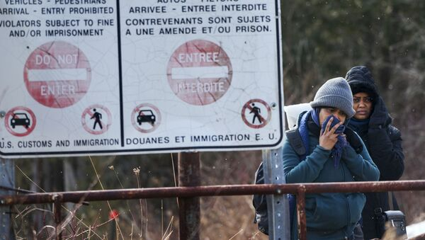 Two people, who later indicated to officials they are from Sudan, hesitate as they listen to a Royal Canadian Mounted Police officer tell them they will be taken into custody just before they crossed into Canada from Perry Mills, N.Y., near Hemmingford, Quebec, Sunday, Feb. 26, 2017 - Sputnik International