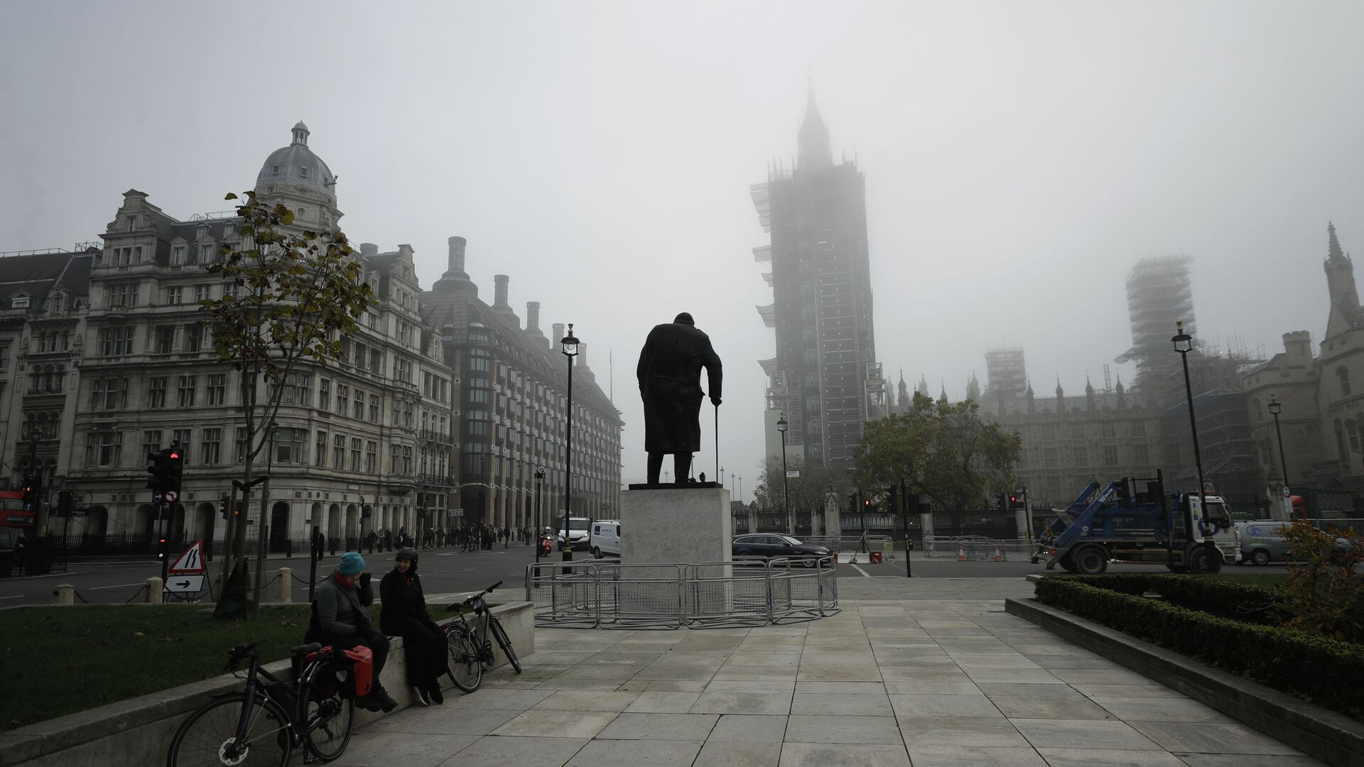 People sit talking near the statue of Winston Churchill and the scaffolded Houses of Parliament and the Elizabeth Tower, known as Big Ben, shrouded in fog, on the first day of Britain's second lockdown designed to save its health care system from being overwhelmed by people with coronavirus, in London, Thursday, Nov. 5, 2020 - Sputnik International, 1920, 13.10.2021