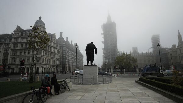 People sit talking near the statue of Winston Churchill and the scaffolded Houses of Parliament and the Elizabeth Tower, known as Big Ben, shrouded in fog, on the first day of Britain's second lockdown designed to save its health care system from being overwhelmed by people with coronavirus, in London, Thursday, Nov. 5, 2020 - Sputnik International