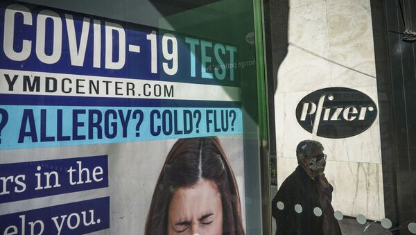 A bus stop ad for COVID-19 testing is shown outside Pfizer world headquarters in New York on Monday Nov. 9, 2020. Pfizer says an early peek at its vaccine data suggests the shots may be 90% effective at preventing COVID-19, but it doesn't mean a vaccine is imminent. - Sputnik International