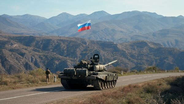 A service member of the Russian peacekeeping troops walks near a tank near the border with Armenia, following the signing of a deal to end the military conflict between Azerbaijan and ethnic Armenian forces, in the region of Nagorno-Karabakh, November 10, 2020. - Sputnik International