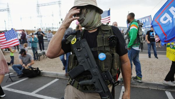 A Trump supporter carries a semi-automatic rifle at a Stop the Steal protest after the 2020 U.S. presidential election was called for Democratic candidate Joe Biden, in front of the Maricopa County Tabulation and Election Center (MCTEC), in Phoenix, Arizona, U.S., November 7, 2020 - Sputnik International