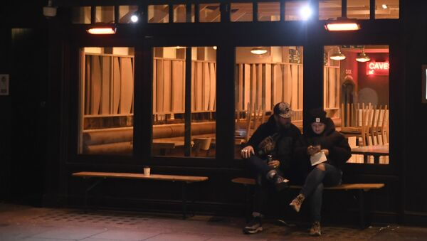 Two people sit outside a closed bar as restaurants and shops in the Soho area are now shut due to a second lockdown in central London, Thursday, Nov. 5, 202 - Sputnik International