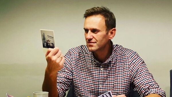 Russian opposition politician Alexei Navalny reads cards and letters from his supporters in an unknown location, in this undated image obtained from social media October 18, 2020 - Sputnik International