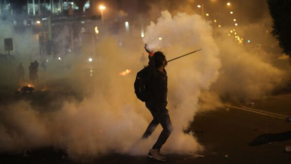 A protester returns a tear gas canister launched by police to disperse protesters who are trying to march to Congress in a demonstration against the removal of President Martin Vizcarra, in Lima, Peru, Thursday, Nov. 12, 2020. - Sputnik International