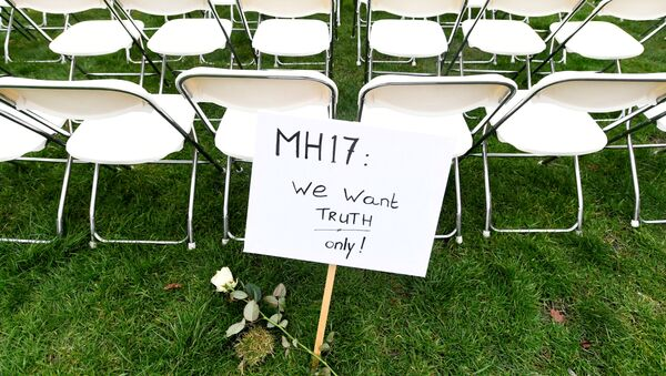 FILE PHOTO: A protest sign stands in front of a row of chairs as family members of victims of the MH17 crash lined up empty chairs for each seat on the plane during a protest outside the Russian Embassy in The Hague, Netherlands 8 March 2020. - Sputnik International