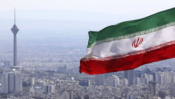 In this March 31, 2020, file photo, Iran's national flag waves as Milad telecommunications tower and buildings are seen in Tehran, Iran - Sputnik International