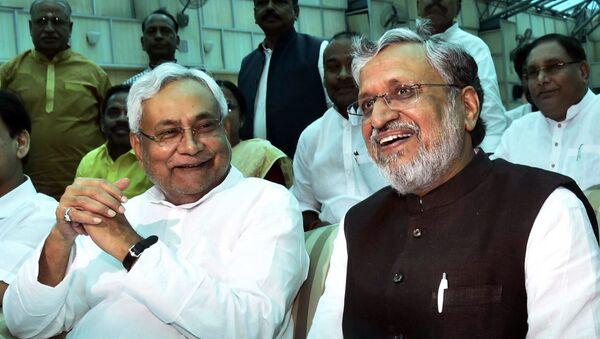 Bihar Chief Minister Nitish Kumar, left, and Deputy Chief Minister Sushil Kumar Modi share a light moment after oath taking ceremony at Raj Bhawan in Patna, India, Thursday, July 27, 2017. - Sputnik International