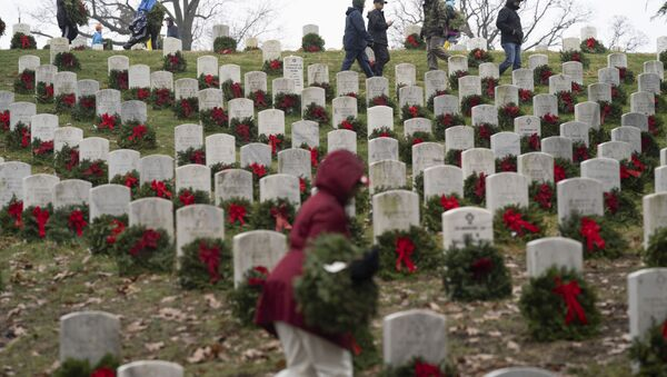 Volunteers lay holiday wreaths at headstones in Arlington National Cemetery during Wreaths Across America Day in Arlington, Va., Saturday, Dec. 14, 2019. Maine businessman Morrill Worcester started the annual event in 1992 at Arlington National Cemetery, and it has expanded to hundreds of veterans' cemeteries and other locations in all 50 states and overseas. (AP Photo/Sait Serkan Gurbuz) - Sputnik International