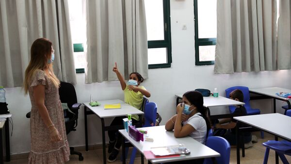 Pupils and a teacher wear protective face masks in a classroom as Israel reopens first to fourth grades, continuing to ease a second nationwide coronavirus disease (COVID-19) lockdown, at a school in Rehovot, Israel November 1, 2020 - Sputnik International
