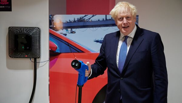 Britain's Prime Minister Boris Johnson holds a charging cable for an electric vehicle (EV), during his visit to the headquarters of energy supplier Octopus Energy in London on October 05, 2020 - Sputnik International
