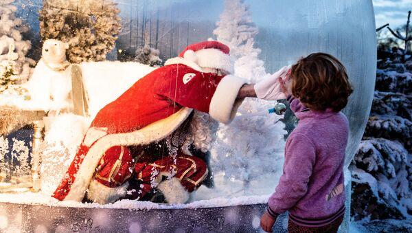 Санта-Клаус поздравляет детей с Рождеством через оргстекло - Sputnik International