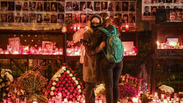 Two young women grieve for those who died at the Colectiv nightclub in Bucharest in 2015. - Sputnik International