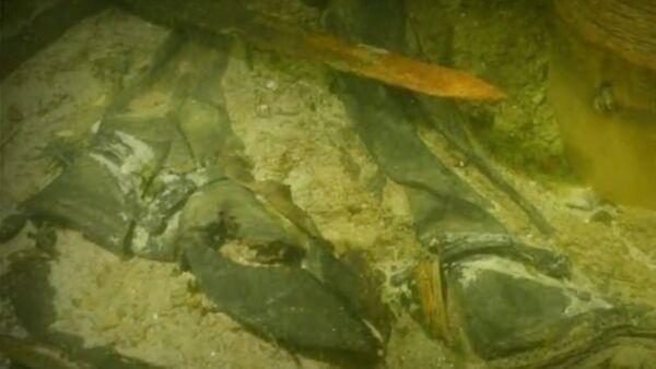 Screenshot image captures the skeletal remains of a medieval solider alongside a variety of artifacts. - Sputnik International