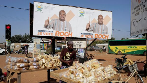 A woman displays bread  for sale near a campaign banner of presidential candidate Roch Kabore in Ouagadougou, Burkina Faso November 20, 2020.  - Sputnik International